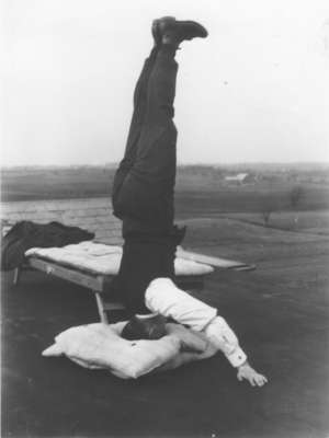 Edgar Fischer standing on his head on the roof of Willison Hall