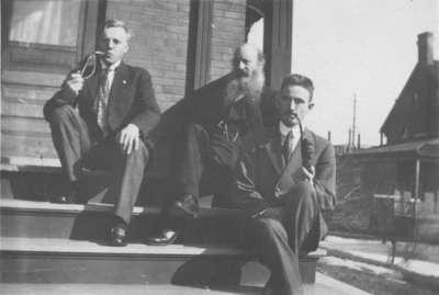 Three men sitting on a porch