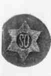 """Photo of a badge/crest with a star on it and letters """"SO"""""""