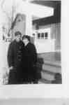 Photograph of an unidentified man and woman standing in front of a building