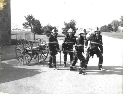 Four firefighters pulling a two wheeled antique pump, Ajax