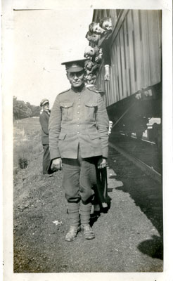 Photograph of a soldier standing beside a train