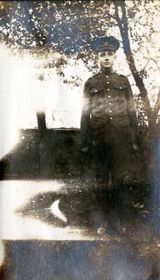 One soldier standing in front of a tree
