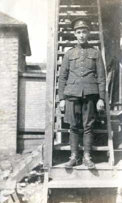 Young soldier in full uniform standing on outdoor stairs