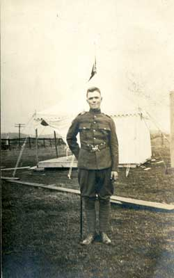 Photograph of soldier in dress uniform in front of a tent