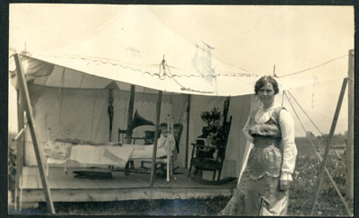 Woman standing in front of white, open sided tent