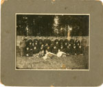 Group photo soldiers on lawn in front of wood fence