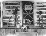 Myrne Grawbarger sitting on the steps of Gardiner's Ice Cream Parlour Deux Rivières