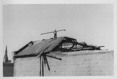 LH2818 Man repairing damaged building post-fire