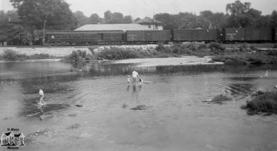 Family Playing in River with Train and Station in Background