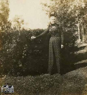 Woman Standing in Front of a Hedge