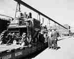 Loading an IHC McCormick model 91 self-propelled combine onto a flatbed railroad car.