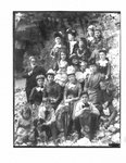 Portrait of a group of women and children, along with one man, and a dog, on a rocky river bank.