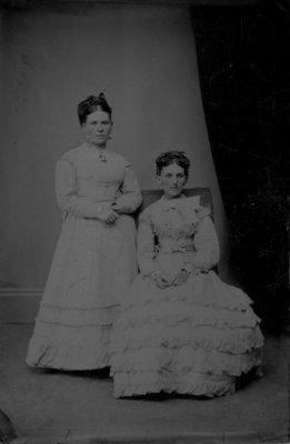 Full length portrait of two women in light dresses.