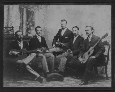 Group portrait of five men, including John Connon, holding musical instruments.