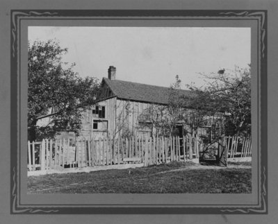A board and batten housewith missing window panes, picket fence and gate.