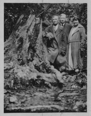 Portrait of John Connon with an unidentified man and woman, standing beside a tree stump.