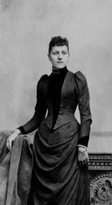 Portrait of an unidentified young woman in a fitted dark dress.