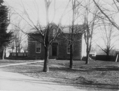 """View of an """"Ontario cottage"""" with gothic window in a gable above the centre front door"""