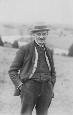 Outdoor portrait of an unidentified man,wearing felt hat, dark waistcoat, light coloured cardigan and dark jacket and trousers.
