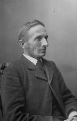 Portrait of an unidentified gentleman, seated, in a business suit.