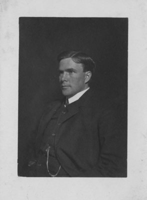 Portrait of an unidentified young man in a business suit, with a watch chain.