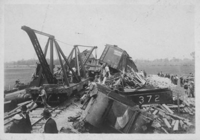 View of a freight train wreck with equipment in place to clear the wreckage.