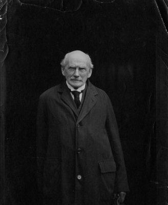 Portrait of an unidentified older gentleman wearing an overcoat.