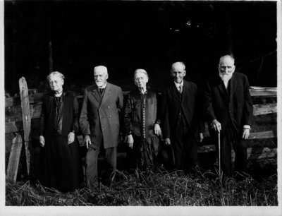 Group portrait of 5 elderly people [3 men, 2 women], in front of a fence.