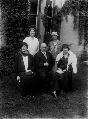 Group portrait of 5 unidentified people [4 women, 1 man] in front of a vine covered building.