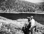 Unidentified Men Survey Forested and Deforested Land Next to a Body of Water