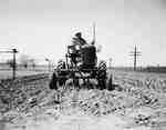 Unidentified Man on a Tractor in a Field